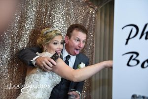 bride and groom inside a photo booth white