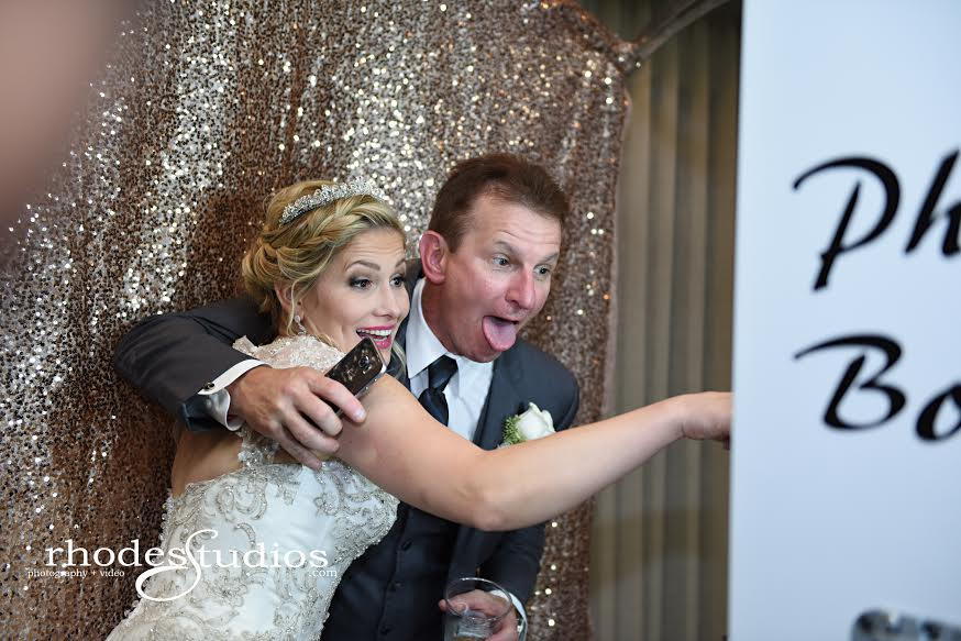 white open air photobooth with rose gold back drop at mission inn wedding bride and groom silly posing