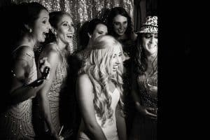 black & white image of bride and bridesmaid in photo booth